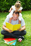 Father reading a book to his daughter Stock Photos