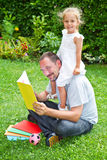Father reading a book to his daughter Stock Image