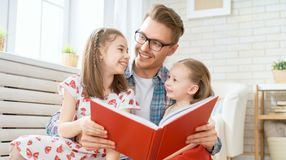 Father reading a book to his daughters. Happy loving family. Young father reading a book to his daughters stock image