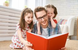 Father reading a book to his daughters. Happy loving family. Young father reading a book to his daughters royalty free stock image