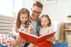 Father reading a book to his daughters. Happy loving family. Young father reading a book to his daughters stock photos