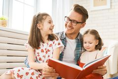 Father reading a book to his daughters. Happy loving family. Young father reading a book to his daughters stock photography