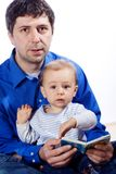 A father reading a book to son. A father reading a book to his young baby son. Isolated on white stock photos