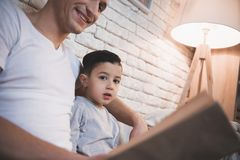 Father is reading fairy tales book to his son at night at home. Father is reading fairy tales book to his son on couch at night at home royalty free stock photo