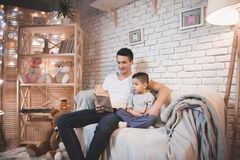 Father is reading fairy tales book to his son at night at home. Father is reading fairy tales book to his son on couch at night at home stock photos
