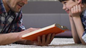 Father reading fairytale to son lying on floor, home leisure preschool education