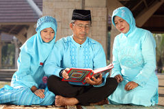 Father Reading Koran Stock Images