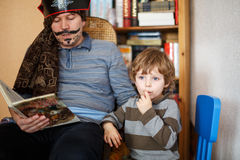 Father reading pirate book to his 4 years son, indoors. Man in pirate costume stock photo