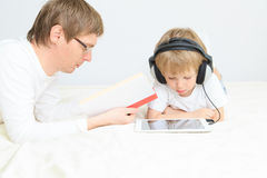 Father reading while son looking at touch pad Royalty Free Stock Photos