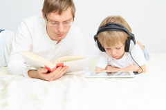 Father reading while son looking at touch pad in headsets Stock Photography