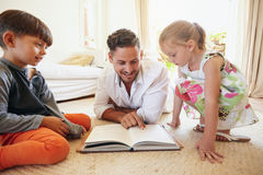 Father reading stories to his children. Family reading a book on the floor in the living room. Father reading stories to his son and daughter at home. Young man stock images