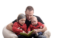 Father reading a story at his two little daughters Stock Images
