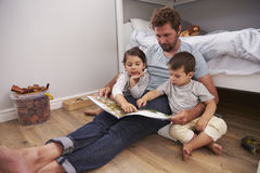 Father Reading Story To Children In Their Bedroom Stock Photos