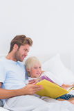 Father reading a story to his cute son. In bed royalty free stock image