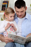 Father reading to his daughter. Father reading a story to his daughter Stock Photos
