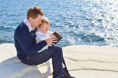 Father reading the Bible to his daughter. By the sea Royalty Free Stock Photos