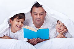 Father reading to his sons. Father reading a story to his little sons - family time together stock images