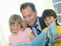 Father reading to son and daughter (4-8), smiling, portrait of boy (tilt) Royalty Free Stock Images