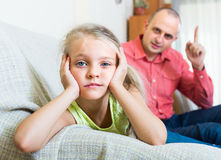 Father rebuking  daughter for offence. Serious father 30s rebuking small daughter for offence at home Stock Photo