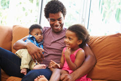 Father Relaxing On Sofa With Young Children. At Home Smiling Stock Images
