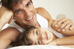 Father Relaxing With Son In Bed Royalty Free Stock Photos