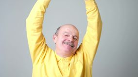 Father relaxing and stretching arms and hands. Handsome senior man in yellow shirt. Father relaxing and stretching arms and hands, smiling happy stock footage