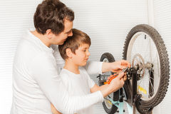Father repairing brakes of bicycle with his  son Stock Photo