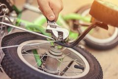 Father repairing his kids bicycle. Removing Bike`s Training Wheels. stock photos