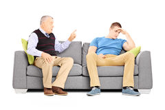 Father reprimending his son seated on a couch Royalty Free Stock Photos