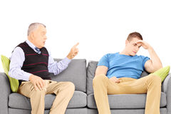 Father reprimending his son seated on a modern sofa Stock Image