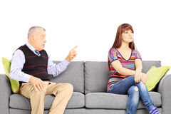 Father reprimending his uninterested daughter seated on a sofa Stock Photography