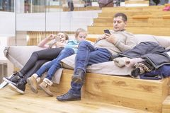 Father with children is waiting on the easy chairs in the store. The father is resting with the kids in the store. royalty free stock photos