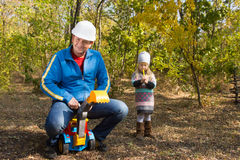 Father riding on his childs toy truck Stock Image