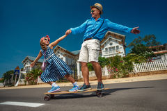 Father riding skateboard with his daughter Royalty Free Stock Image
