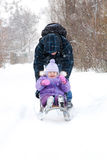 Father rolling child on a sled Stock Photo
