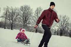 Father rolling daughter on sled in winter park Royalty Free Stock Images