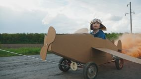 Father rolls his son on a homemade cardboard plane. Father rolls his little son on a self-made cardboard plane on the road in the countryside. The concept of a stock video