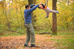 Father rotates child for hands in wood Stock Photos