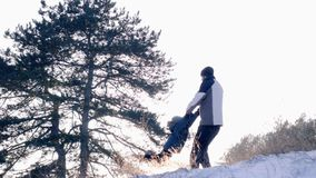 Father rotating his son holding his hands in slow motion in snow-covered forest at winter outdoor. Kherson, Ukraine, 10 December 2017: father rotating his son stock video