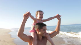 Father Running Along Beach Carrying Daughter On Shoulders stock video footage