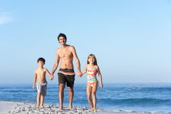 Father Running With Children Along Sandy Beach. Smiling At Camera Stock Photo