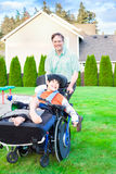 Father running with disabled son in wheelchair Stock Image