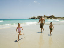 Father running after his kids on the beach Royalty Free Stock Image