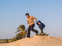 Father runs over a dune of the Sahara desert holding hands to hi. Father runs over a dune in the Sahara desert, holding hands with his 3-year-old son, Douz Royalty Free Stock Image