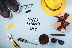 Father`s day background or card Tools Yellow hat Glasses Sneakers Cup of coffee Cigar Gift on a blue background Text Flat lay Top stock photos