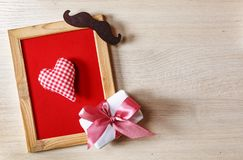 Father`s Day Background Heart in a frame on a red background, with a gift box and black mustache. Free space for text. Happy fath royalty free stock image