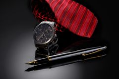 Father& x27;s Day or business concept image. Elegant man& x27;s watch, fountain pen and red tie on black gradient background. Stock Images