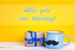 Father`s Day card with  blue mug  and gift box on yellow backgro. Father`s Day card with  blue mug with a mustache and gift box on yellow background.  German Royalty Free Stock Images