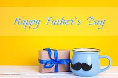 Father`s Day card with  blue mug with a mustache and gift box on. Father`s Day card with blue mug with a mustache and gift box on yellow. Happy Father`s Day Royalty Free Stock Photography