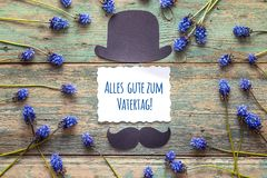 Father`s Day card with cardboard hat and mustache and blue flowe. Rs. German greeting `Alles gute zum Vatertag!`, which means `Happy Father`s Day Stock Images